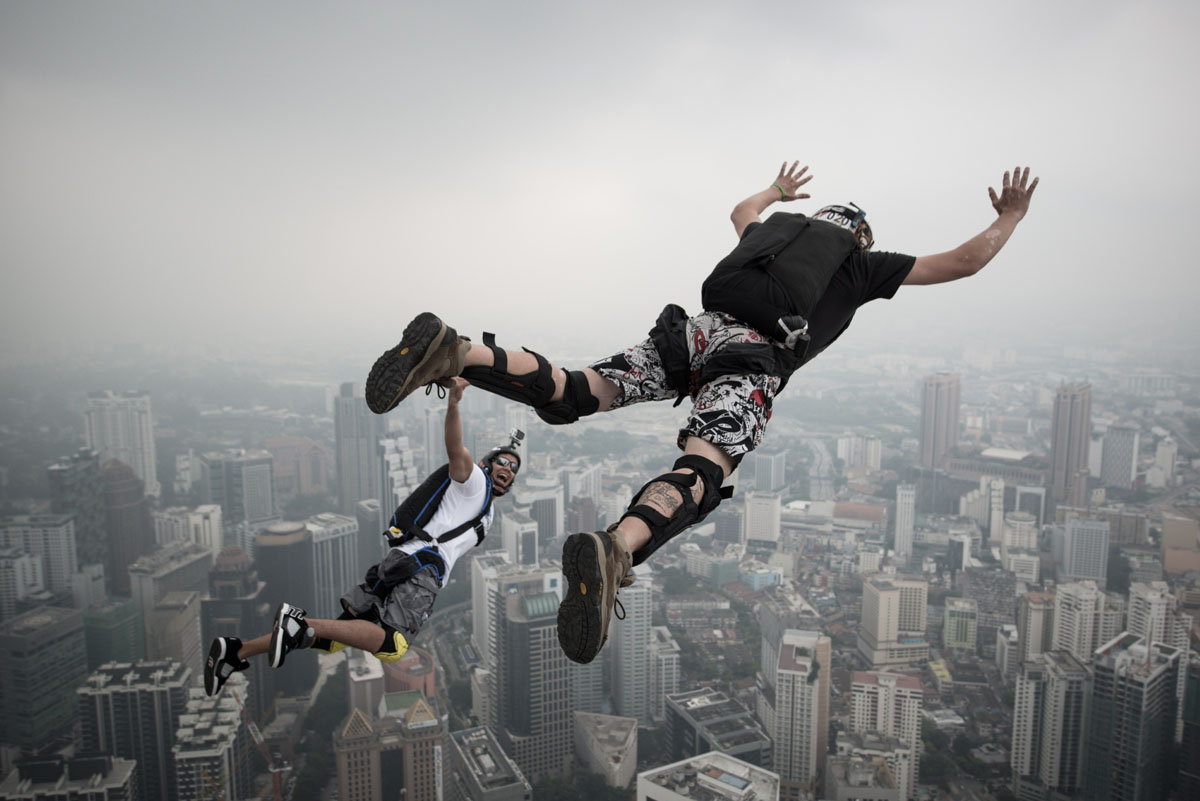Base jumper David Laffargue (R) and Rodolphe Roger Coianiz (L) from France leap from the 300-metres Open Deck of the Malaysia's landmark Kuala Lumpur Tower during the International Tower Jump in Kuala Lumpur on September 27, 2013. Some 103 professional base jumpers from 20 countries are taking part in the annual event. AFP PHOTO / MOHD RASFANMOHD RASFAN/AFP/Getty Images ORG XMIT:
